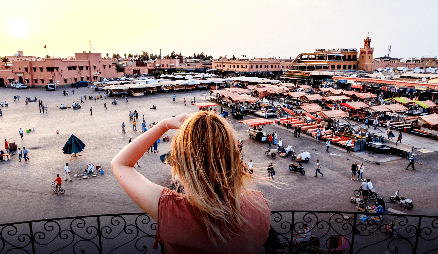 Blonde woman takes photo of a market square from balcony